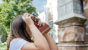 Retrato de la mujer turística morena joven que usa la cámara manual del vintage Fotografía de archivo