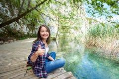 Retrato de la mujer turística sonriente joven que se sienta en el puente de madera, mostrando los pulgares para arriba imagenes de archivo