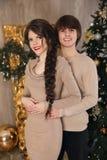Retrato de la Navidad de los pares adolescentes jovenes que abrazan llevar en beige Foto de archivo libre de regalías