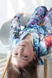 Retrato de la niña agradable al revés en una silla blanca Imagen de archivo