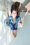 Retrato de la niña agradable al revés en una silla blanca Fotos de archivo libres de regalías