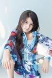 Retrato de la niña agradable en una silla blanca Foto de archivo libre de regalías