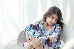 Retrato de la niña agradable en una silla blanca que abraza rodillas Imagenes de archivo