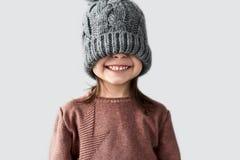 Retrato de la niña alegre divertida ocultada los ojos en el sombrero gris caliente del invierno, el suéter sonriente y que lleva  fotografía de archivo