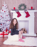 Retrato de la niña bastante dulce cerca de una chimenea en la Navidad Foto de archivo