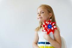 Retrato de la niña bonita con el molino de viento rojo en el día de verano Fotos de archivo libres de regalías