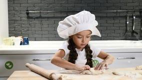 Retrato de la niña bonita en sombrero del cocinero con el rodillo en manos El pequeño cocinero rueda la pasta y rasga en pedazos almacen de metraje de vídeo
