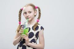 Retrato de la niña caucásica linda y sonriente con las coletas que presentan en la polca Dot Dress Foto de archivo