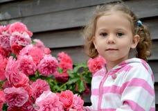 Retrato de la niña cerca de las rosas florecientes Fotos de archivo libres de regalías