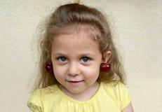 Retrato de la niña con las bayas de la cereza dulce como pendiente en los oídos fotografía de archivo libre de regalías
