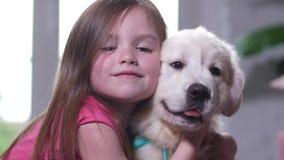Retrato de la niña dulce que abraza con el perrito almacen de metraje de vídeo