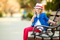 Retrato de la niña en banco en un parque que muestra el pulgar para arriba Fotografía de archivo