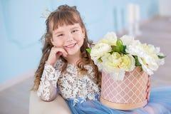 Retrato de la niña en el vestido lujoso que presenta en estudio azul adornado con el ramo de flores en el diván retro del sofá imagen de archivo