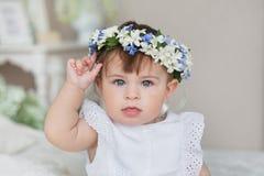 Retrato de la niña en un vestido blanco y con una diadema en una cabeza Imagen de archivo libre de regalías