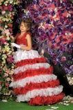Retrato de la niña en vestido con la flor Fotos de archivo
