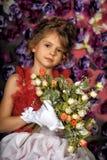 Retrato de la niña en vestido con la flor Foto de archivo