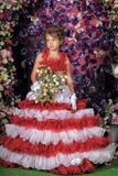 Retrato de la niña en vestido con la flor Imagen de archivo libre de regalías