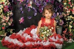 Retrato de la niña en vestido con la flor Imagenes de archivo