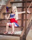 Retrato de la niña feliz con el molinillo de viento que se sienta en las escaleras imagen de archivo libre de regalías