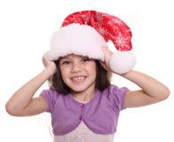 Retrato de la niña feliz en el sombrero de Papá Noel Foto de archivo