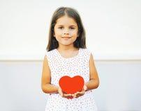 Retrato de la niña linda con el corazón de papel rojo Foto de archivo libre de regalías