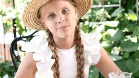 Retrato de la niña linda con un sombrero de paja en la consumición hacia fuera en un café de la calle Ella come un cruasán del qu almacen de metraje de vídeo