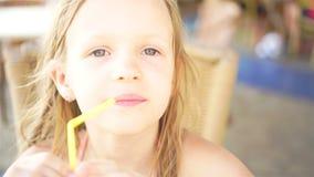 Retrato de la niña linda que se sienta por la tabla de cena anddrinking el jugo fresco metrajes