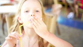 Retrato de la niña linda que se sienta por la tabla de cena y el jugo fresco de consumición metrajes