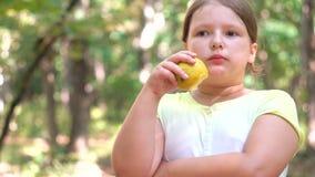 Retrato de la niña que come la manzana al aire libre de la manzana al día de verano almacen de metraje de vídeo