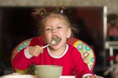 Retrato de la niña que lame la cuchara que come las gachas de avena que se sientan en silla de alimentación fotos de archivo