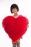 Retrato de la niña que lleva a cabo el corazón rojo sobre asiático fotos de archivo libres de regalías