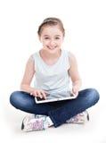 Retrato de la niña que se sienta con la tableta Imágenes de archivo libres de regalías