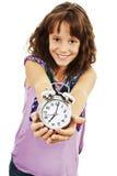 Retrato de la niña que sostiene el reloj de alarma Foto de archivo