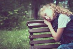 Retrato de la niña rubia triste que se sienta en banco Imagen de archivo