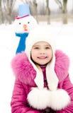 Retrato de la niña sonriente con el muñeco de nieve Foto de archivo libre de regalías