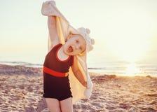Retrato de la niña sonriente feliz adorable linda del niño con la toalla en la playa que hace las caras de las actitudes que se d Fotos de archivo libres de regalías