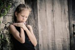 Retrato de la niña triste que se coloca cerca de la pared de piedra en el día Foto de archivo