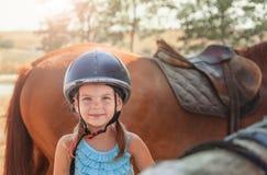 Retrato de la niña y del caballo marrón Muchacha con los cascos Imagen de archivo libre de regalías