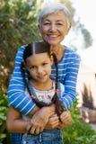 Retrato de la nieta de abarcamiento sonriente de la mujer mayor Imágenes de archivo libres de regalías