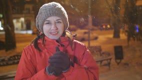 Retrato de la nieve que sopla de la muchacha feliz hermosa en la ciudad del invierno de la noche, mujer que mira la cámara metrajes