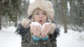 Retrato de la nieve que sopla sonriente de la mujer a una cámara Fotos de archivo