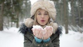 Retrato de la nieve que sopla sonriente de la mujer a una cámara Imagen de archivo