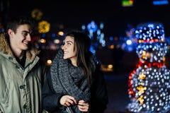 Retrato de la noche de un par feliz que sonríe gozando de aoutdoors del invierno y de la nieve Alegría del invierno Emociones pos imagen de archivo libre de regalías