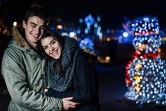Retrato de la noche de un par feliz que sonríe gozando de aoutdoors del invierno y de la nieve Alegría del invierno Emociones pos imagen de archivo