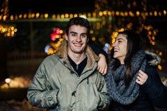Retrato de la noche de un par feliz que sonríe gozando de aoutdoors del invierno y de la nieve Alegría del invierno Emociones pos fotos de archivo