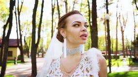 Retrato de la novia bonita con maquillaje y de cristales en cara que caminan en parque iluminado por el sol almacen de video