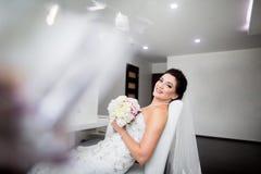 Retrato de la novia feliz hermosa que se sienta en el sof? imagenes de archivo