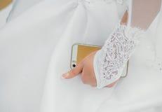 Retrato de la novia feliz que sostiene el teléfono celular del oro Foto de archivo