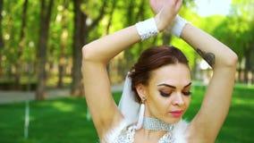 Retrato de la novia joven con maquillaje y de cristales en el baile de la cara en parque iluminado por el sol almacen de video