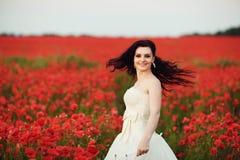 Retrato de la novia joven hermosa en campo por completo de amapolas rojas Imagenes de archivo